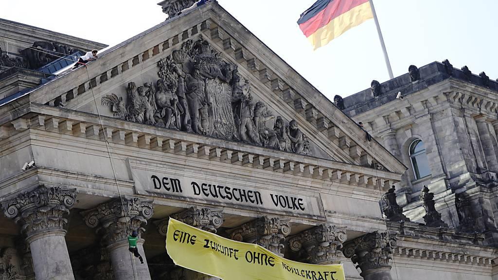 Greenpeace-Aktivisten seilen sich mit einem Transparent vom Reichstagsgebäude ab, auf dem geschrieben steht: «Eine Zukunft ohne Kohlekraft». Der Bundestag verabschiedet heute ein neues Kohlegesetz. Foto: Kay Nietfeld/dpa