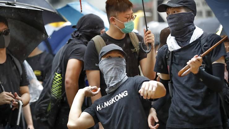 Ein Protestierender bereitet sich auf einen Eierwurf vor. Am Freitagabend und am Samstag sind in Hongkong wiederum Zehntausende auf die Strasse gegangen.