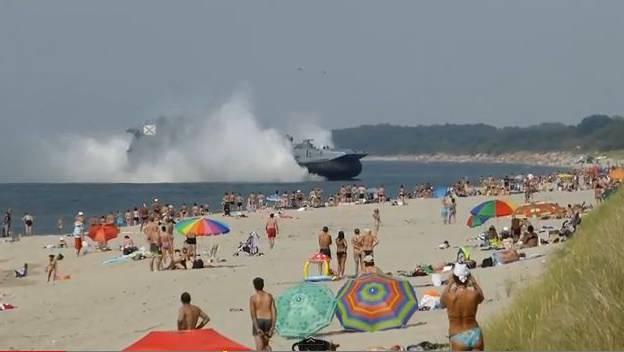 Russisches Marineboot fährt auf Badestrand.