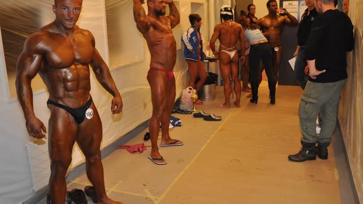 Kurz vor dem Auftritt bringen sich die männlichen Bodybuilder hinter den Kulissen in Höchstform