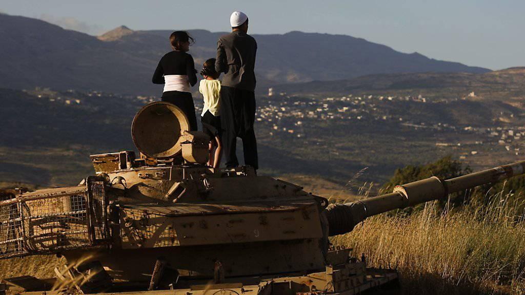 Junge drusische Geistliche stehen auf einem zerstörten Panzer auf den Golan-Höhen: Die syrische Minderheit hat sich vom Assad-Regime mittlerweile distanziert. (Archiv)