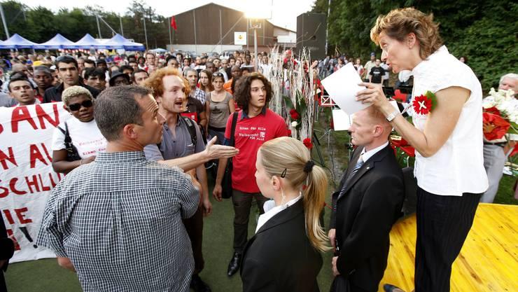 Justizministerin Eveline Widmer-Schlumpf diskutiert am Rande der 1. Augustfeier in Eiken mit Sans-Papiers-Vertretern.