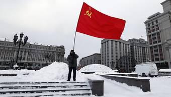 Ein Kommunist schwenkt die Sowjetunion-Flagge auf dem Roten Platz in Moskau (Archiv)