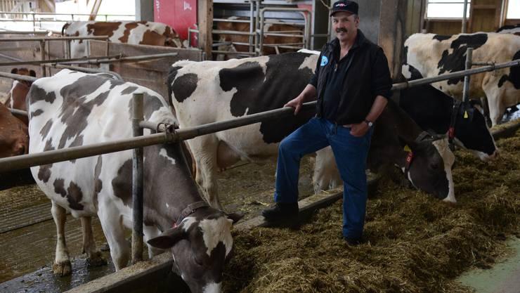 Bauer Hans-Ueli Lüscher mit Berna im Stall in Muhen. Im Hintergrund stehen Kühe vor dem Melkroboter an. An einem Tag kommen hier rund 2000 Kilogramm Milch zusammen.
