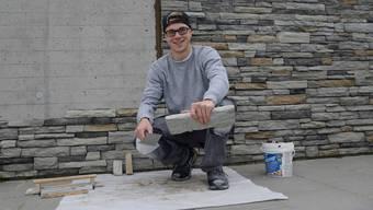 Plattenlegen findet nicht nur in Bad und Küche statt. Der angehende Plattenleger Cédric Brunner plättelt derzeit mit einer Naturstein- Imitation eine Mauer im Garten eines Einfamilienhauses.