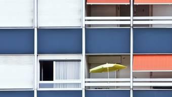 Ein Sonnenschirm steht auf einem Balkon einer Blockwohnung in Rorschach (Archiv)