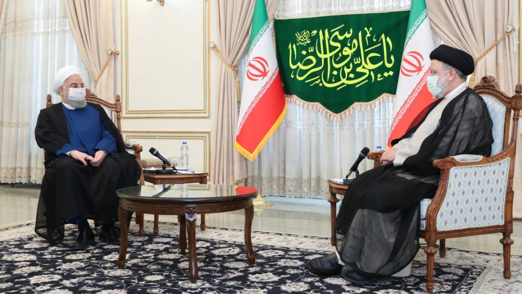 HANDOUT - Hassan Ruhani (l), amtierender Präsident des Iran, gratuliert seinem Nachfolger Ebrahim Raeissi. Foto: -/Iranian Presidency/dpa - ATTENTION: editorial use only and only if the credit mentioned above is referenced in full