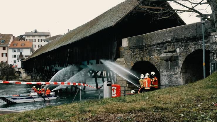 Die historische Holzbrücke in Olten brennt - die Feuerwehr löscht.