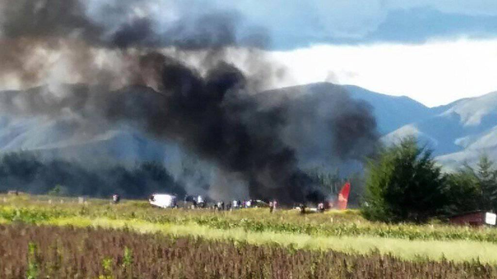 Rettungskräfte helfen den Passagieren des in Flammen aufgegangenen Flugzeugs in Peru.  Alle Menschen an Bord überlebten, doch es gab viele Leichtverletzte.