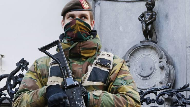 """Ein Soldat bewacht die """"Manneken Pis""""-Statue in Brüssel. In Belgien gilt derzeit die zweithöchste Terror-Alarmstufe. (Archiv)"""