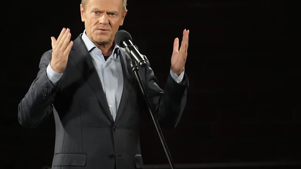 Donald Tusk, ehemaliger Ministerpräsident von Polen, hält eine Rede auf einem Podium während einer Demonstration zur Unterstützung der polnischen EU-Mitgliedschaft. In Polen haben landesweit Tausende von Menschen gegen ein umstrittenes Urteil des Verfassungsgerichts und für den Verbleib ihres Landes in der EU demonstriert. Foto: Czarek Sokolowski/AP/dpa