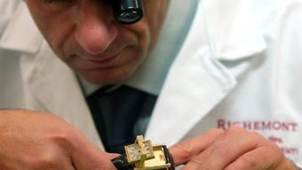 Ein Uhrmacher bearbeitet eine Uhr (Archiv)