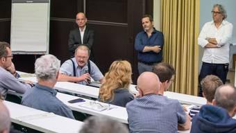 Sigmund Bachmann (mit Mikrofon) beantwortet Fragen aus dem Publikum. Im Hintergrund die drei Referenten (von links): Stadtplaner Lorenz Schmid sowie die beiden Architekten Daniel Schneider und Bertram Ernst, welche bei der Ausarbeitung des Masterplans mitgewirkt haben