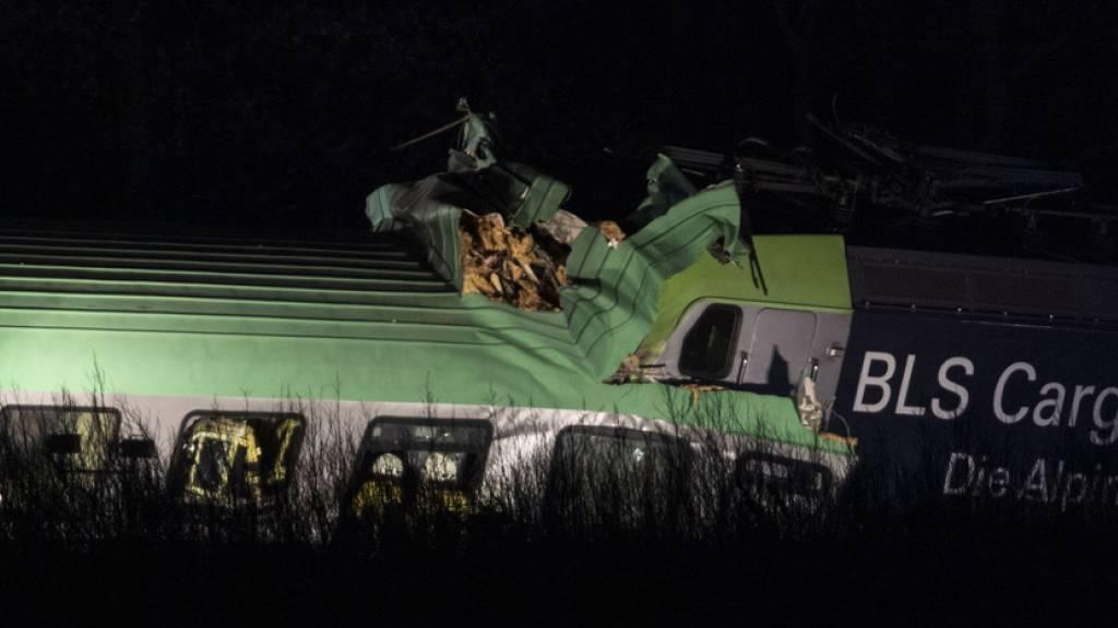 Feuerwehrfahrzeuge stehen bei dem verunglückten Zug. Der BLS-Güterzug, der Lastwagen geladen hatte, ist auf der Rheintalstrecke mit Teilen einer Brücke kollidiert.