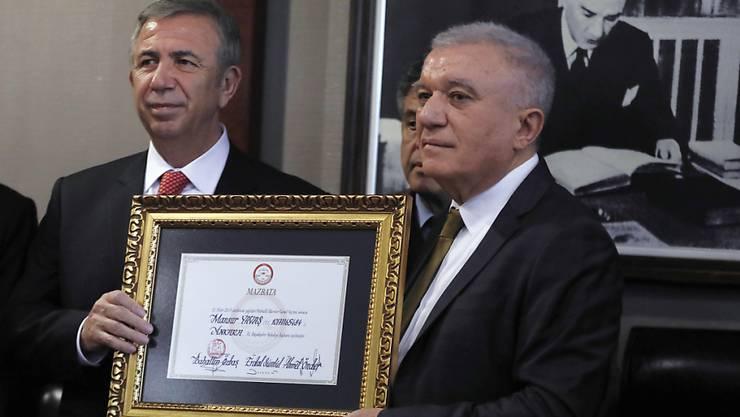 Oppositionskandidat Mansur Yavas (l.) erhält vom Chef der türkischen Wahlkommission ein Dokument, das seine Wahl zum Bürgermeister von Ankara bestätigt.