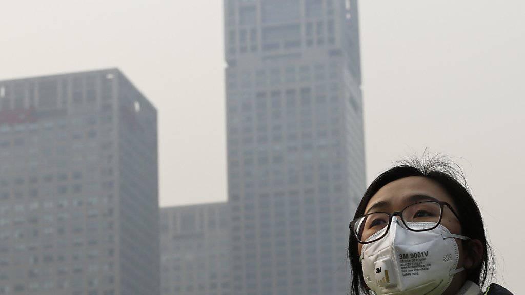 Peking im Smog: Wer auf die Strasse muss, trägt hier eine Maske zum Schutz vor dem Feinstaub.