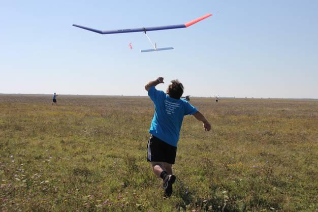 Der Wettkampf beginnt: Heinz Bleuer gibt das Modell ab, damit Michael (hinten links im Feld) in der Luft nach guter Thermik suchen kann.