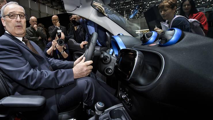 Bundesrat Guy Parmelin hat sich an der Eröffnung des Genfer Autosalons probehalber in einen Smart EQ fortwo gesetzt, der 100 Prozent elektrisch angetrieben wird.