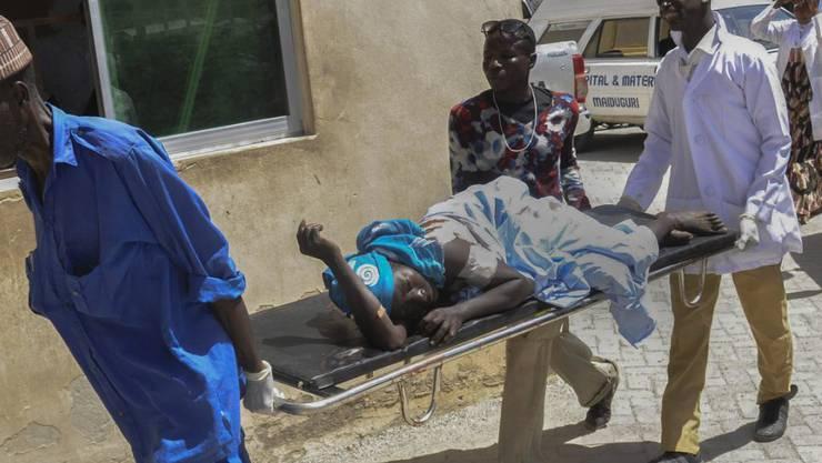 Rettungskräfte bringen einen Verletzten nach dem Bombenanschlag im Nordosten Nigerias in Sicherheit (Archivbild).