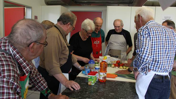 Die Senioren schauen der Kochkursleiterin aufmerksam zu