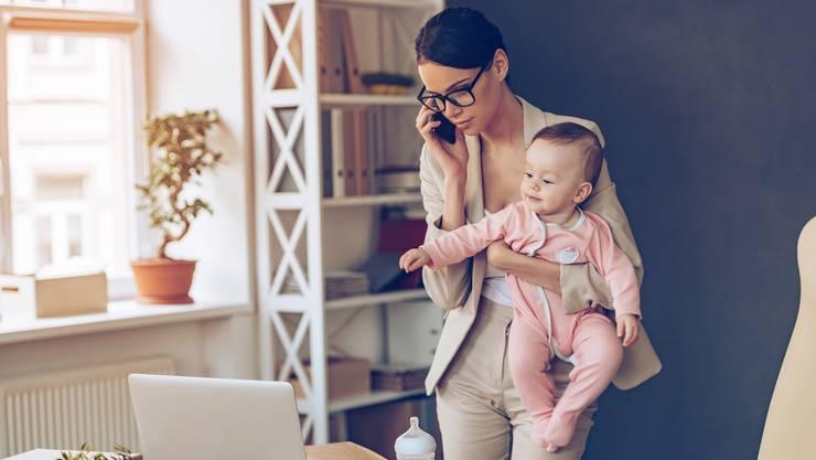 Arbeitende Mutter mit Baby im Arm