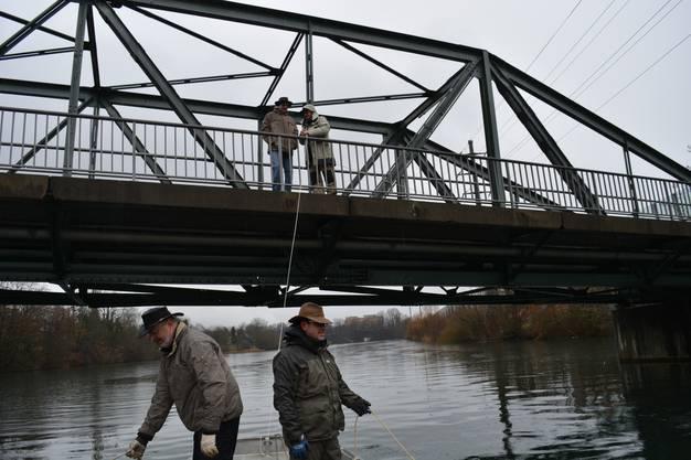 Zwei Männer halten die Taucher und zwei stehen auf der Brücke und befestigen das Boot