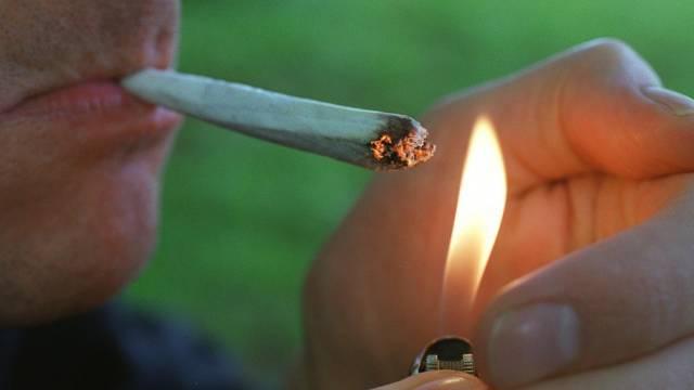 Raucher zündet einen Joint an (Symbolbild)