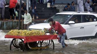Ein Strassenhändler schiebt seinen Wagen durch die überschwemmten Strassen von Mumbai.