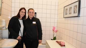 Benita Spengler und Ibadete Aliaj zeigen die neu dekorierte Toilette bei der Oftringer Socar-Tankstelle.