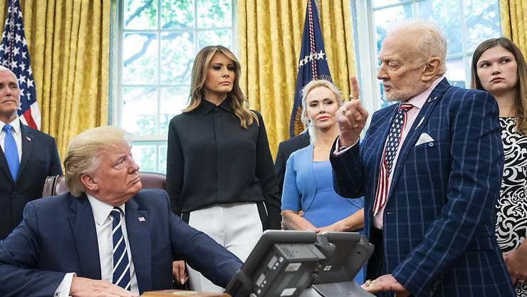 US-Präsident Donald J. Trump (sitzend) im Gespräch mit dem früheren Astronauten Buzz Aldrin (rechts, stehend). Nicht auf dem Bild ist der Apollo-11-Astronaut Michael Collins.