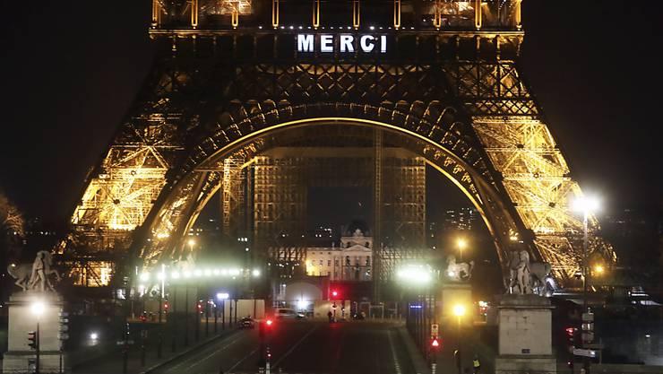 """Der Eiffelturm in Paris bedankt sich mit """"Merci"""" bei allen Helfern in der Coronavirus-Krise."""