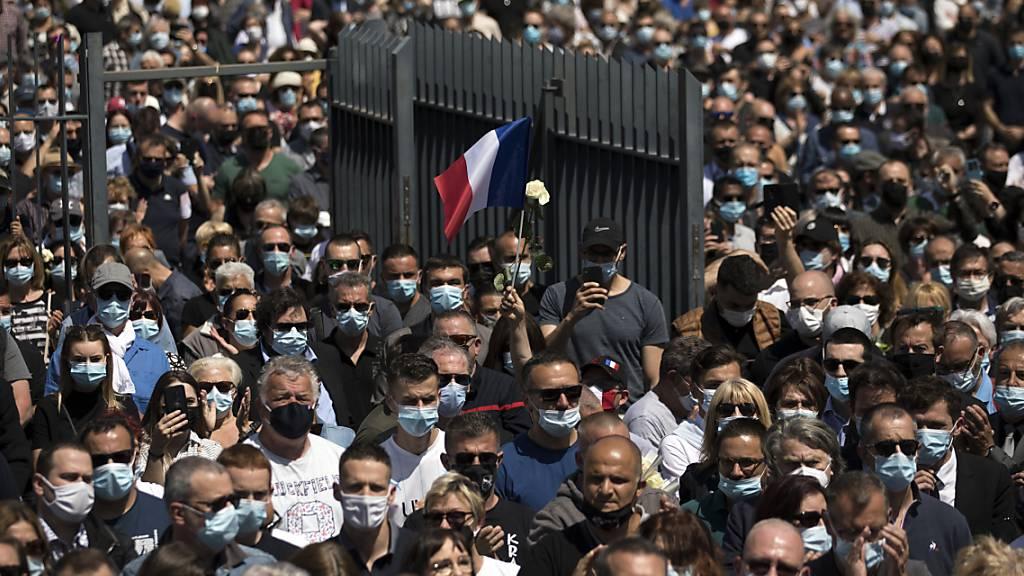 Polizeibeamte und Zivilisten versammeln sich an einer Polizeistation in Avignon, um des Todes eines Polizisten zu gedenken, der an einem Drogenumschlagplatz getötet wurde. Foto: Daniel Cole/AP/dpa