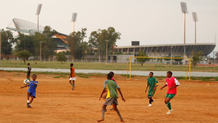 Locals play soccer in front of the Royal Bafokeng sports stadium in Phokeng township, Rustenburg, November 26, 2009. Rusternburg is one of the South African cities hosting the 2010 FIFA Soccer World Cup. REUTERS/Siphiwe Sibeko (SOUTH AFRICA SPORT SOCCER)