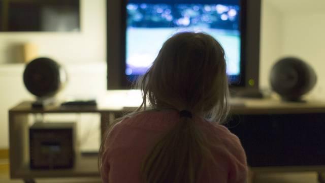 Ein Mädchen schaut Fernsehen in einer Wohnung (Symbolbild)
