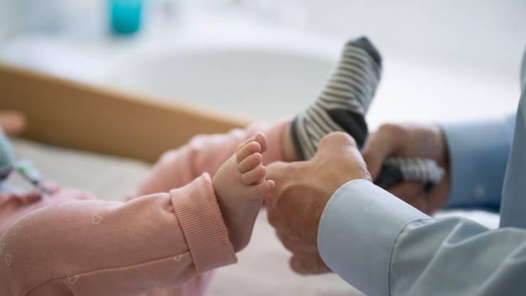 Papi packt an: Ein Vater zieht seiner fünf Monate alten Tochter Socken an. Archivbild Gaetan Bally/Keystone