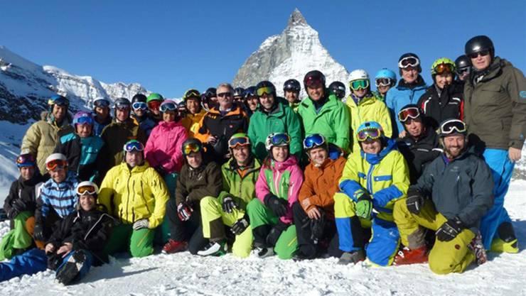 Fröhliche Stimmung beim Zentralkurs der Schneesportexperten vor majestätischem Hintergrund.