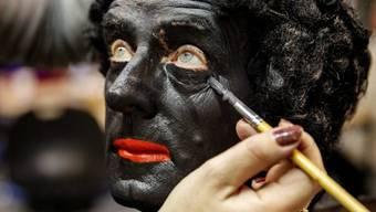 """Ein Mann wird als """"Zwarte Piet"""" geschminkt (Archiv)"""