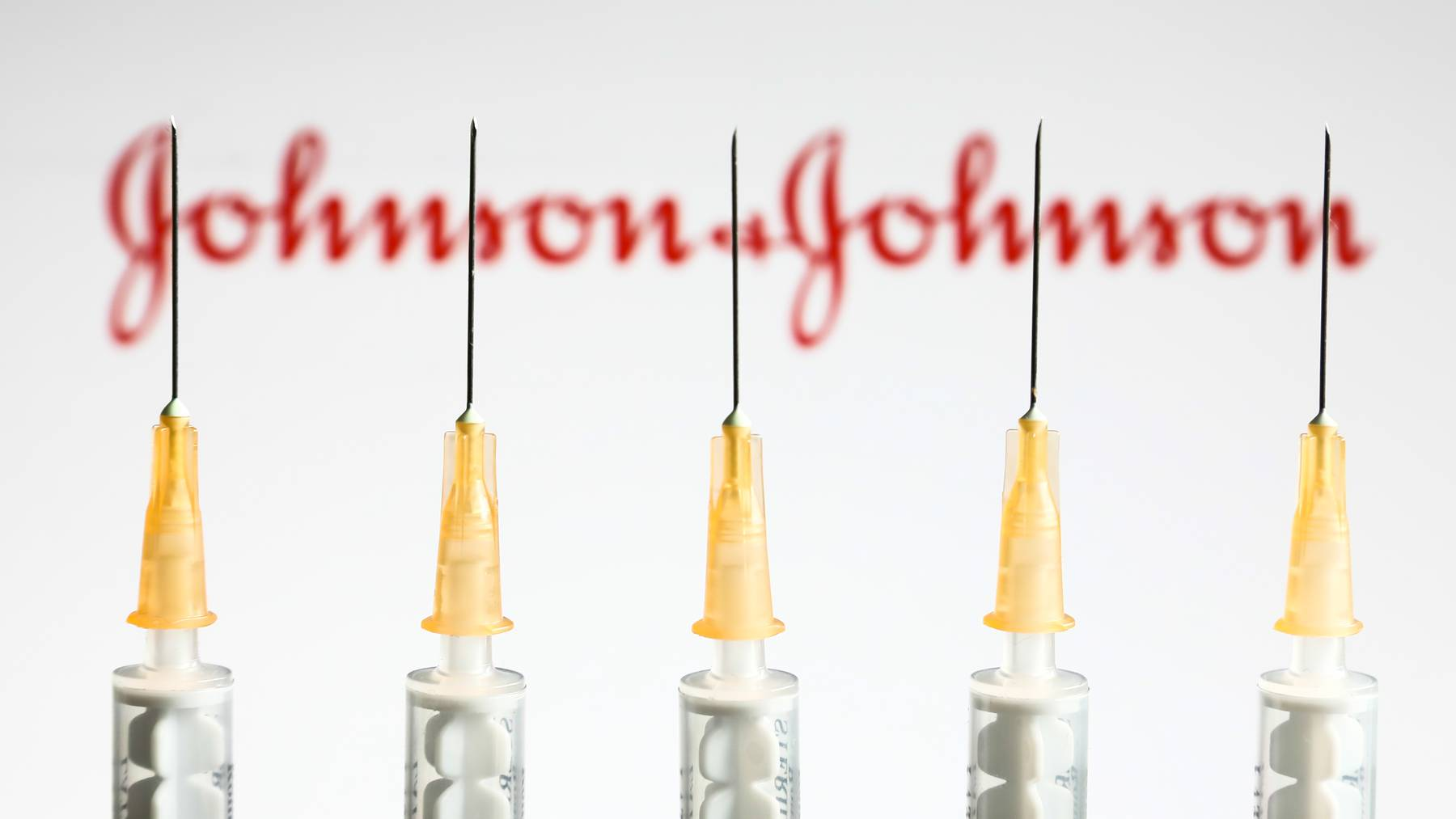 Medical syringes are seen with Johnson&Johnson logo displayed on a screen in the background in this illustration photo taken in Krakow, Poland on April 14, 2021.