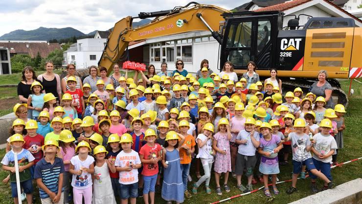 Wangens Schulkinder mit Bauhelm freuen sich auf die Veränderung; im Hintergrund der Pavillon, der dem Neubau weichen muss.