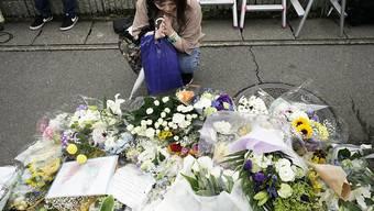 Nach dem Brandanschlag auf ein Trickfilm-Studio in Kyoto legen Anwohner Blumen nieder und beten für die Opfer.