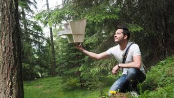 Der Initiator Bertrand Bitz zeigt ein Modell einer Baumhütte, die im Wald in der Walliser Gemeinde Nax gebaut werden sollen.