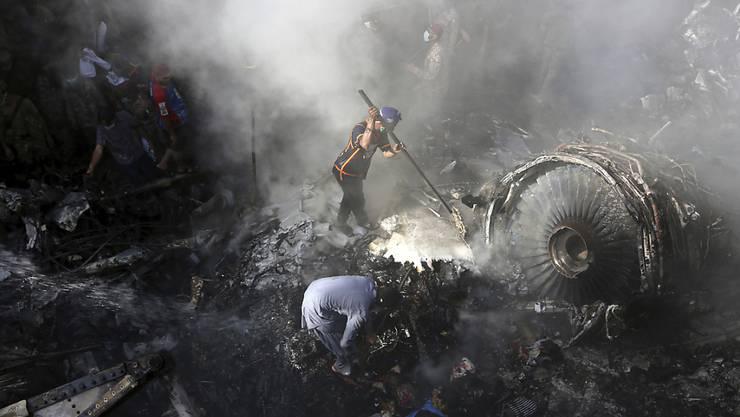 dpatopbilder - ARCHIV - In Karachi suchen freiwillige Helfer und Einsatzkräfte nach dem Absturz eines Passagierflugzeugs in einem Wohngebiet nach Überlebenden. Foto: Fareed Khan/AP/dpa