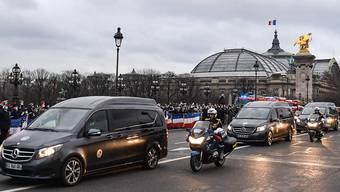 Fahrzeuge mit den Särgen von drei französischen Soldaten fahren in Paris über die Brücke Alexandre III an einer Gruppe von Menschen vorbei, die den Soldaten gedenken. Foto: Alain Jocard/AFP/dpa