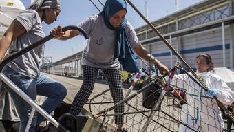 """Frauen gehen nach der Ankunft in Barcelona von Bord der """"Open Arms""""."""