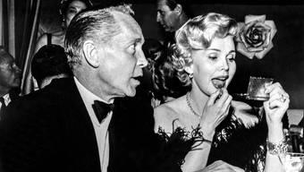 Die Filmschauspielerin Zsa Zsa Gabor, rechts, zieht sich in einem Restaurant in Hollywood die Lippen nach (1955).