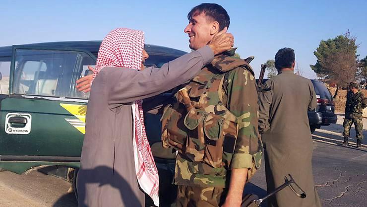 Syrische Regierungstruppen haben in Kurdengebieten nahe der Grenze zur Türkei Stellung bezogen. Sie wurden in der Stadt Tall Tamar nordwestlich von Al-Hassaka von Einwohnern begrüsst.