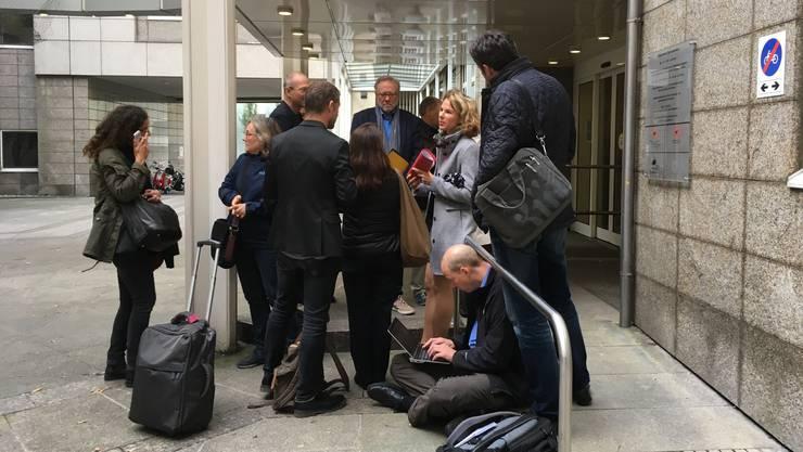 Ein Teil der Medienvertreter wartet vor dem Haupteingang des Gerichts.