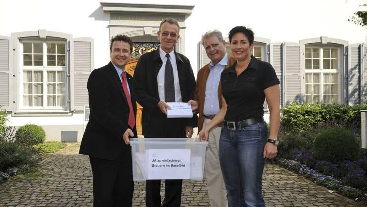 Deponiert: Die FDP-Exponenten Michael Herrmann (links), Hanspeter Frey (2. v. r.) und Daniela Schneeberger (rechts) übergeben dem Baselbieter Landschreiber Walter Mundschin die Kiste mit den 4500 Unterschriften ihrer Steuer-Initiative.