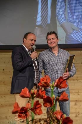 Landwirtschaftsdirektor und Regierungsrat Markus Dieth übergibt Simon Lüscher in der Vianco Arena in Brunegg die Auszeichnung als Aargauer Bauer des Jahres.