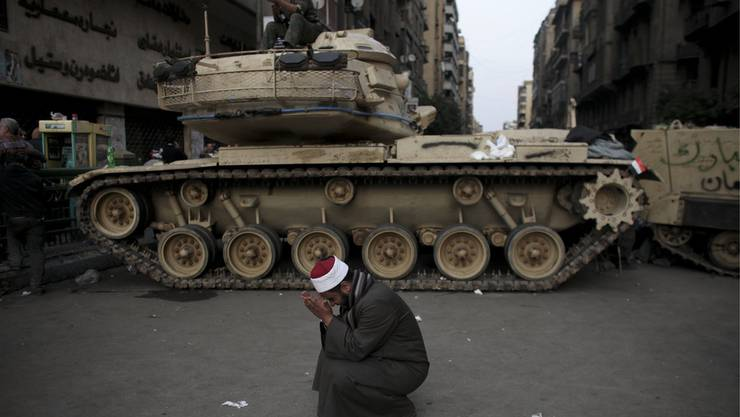 Gläubiger betet mitten in den Unruhen am Rande des Tahrir-Platzes